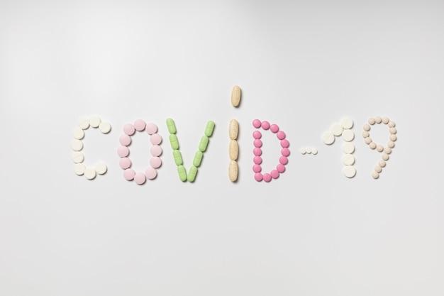 """Napis """"covid-19"""" z wielobarwnych tabletek"""
