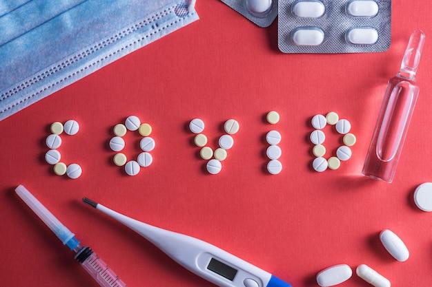 Napis covid wykonany z białych okrągłych tabletek. jednorazowa strzykawka i fiolka leku na czerwonym tle. szczepionka przeciwko koronawirusowi covid-19. miejsce na tekst