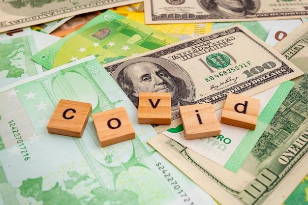 Napis covid19 na drewnianych kostkach na fakturze dolarów amerykańskich i banknotów euro