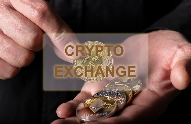 Napis crypto exchange nad męską ręką z monetami kryptowalut
