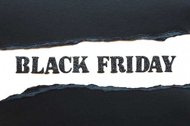 Napis czarny piątek w czarne błyszczące litery na białym tle i rozdarty czarny papier.
