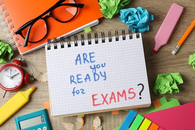 Napis czy jesteś gotowy na egzaminy? i różne stacjonarne na drewnianym stole, widok z góry