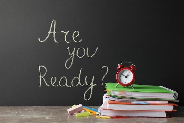 Napis czy jesteś gotowy na egzaminy? na czarnej ścianie i stacjonarne na szarym stole