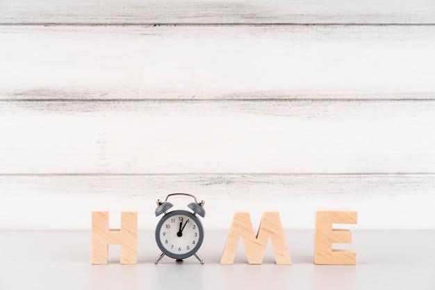 Napis do domu z drewnianymi literami i zegarem