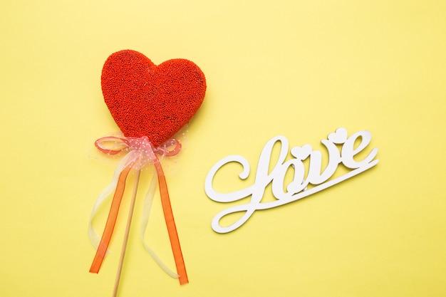 Napis drewniane litery miłości na żółtym tle na białym tle. serce w formie cukierków na patyku.