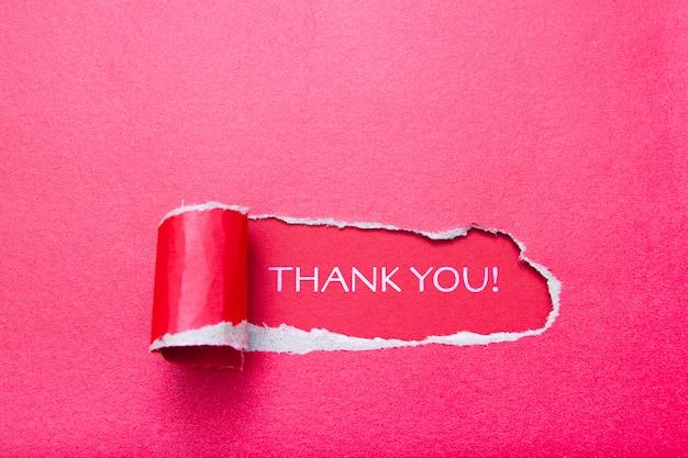 Napis dziękuję w dziurze w kartce czerwonego papieru na czerwonym tle. układ z rozdartym papierem z miejscem na tekst.