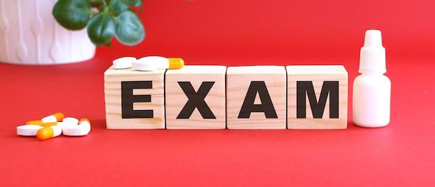Napis exam składa się z drewnianych kostek na czerwonym tle z lekarstwami.