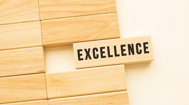 Napis excellence na drewnianym pasku leżącym na białym stole. pojęcie.