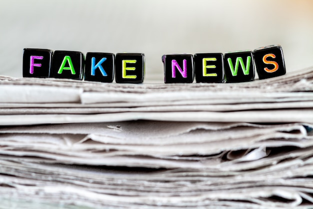 Napis fałszywe wiadomości na stosie gazet.