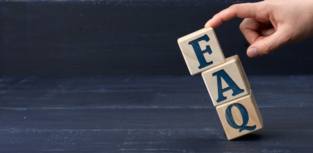 Napis faq (często zadawane pytania) na drewnianych klockach na niebieskiej powierzchni