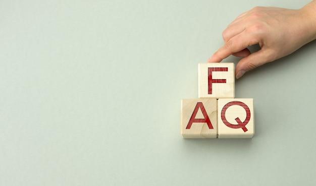 Napis faq (najczęściej zadawane pytania) na drewnianych klockach na szarej powierzchni. koncepcja kontroli jakości, pomoc i wskazówki, ręka trzyma kostki, miejsce na kopię copy