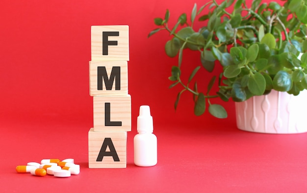 Napis fmla składa się z drewnianych kostek na czerwonej powierzchni z lekarstwami.