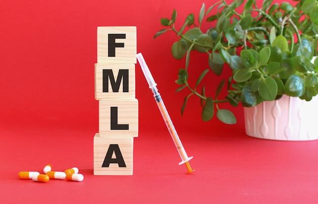 Napis fmla wykonany jest z drewnianych kostek na czerwono z lekarstwami.