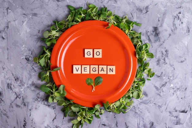 Napis go wegańskie litery na pomarańczowym talerzu w ramce z zieloną sałatą ze świeżej kukurydzy