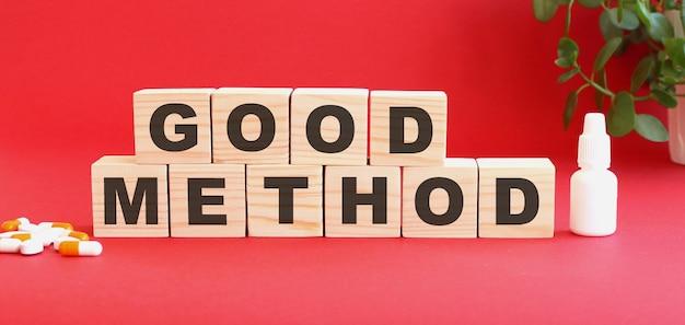 Napis good method składa się z drewnianych kostek na czerwonym tle z lekarstwami.