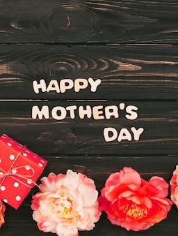 Napis happy mothers day z małym upominkiem i kwiatami