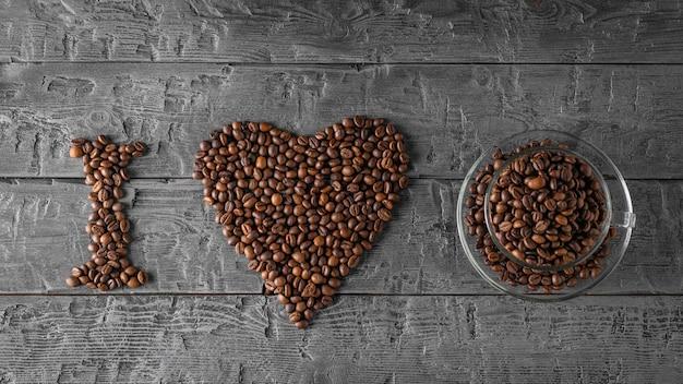 Napis i love wyłożony ziarnami kawy na czarnym drewnianym stole. widok z góry. leżał na płasko. ziarna do przygotowania popularnego napoju.