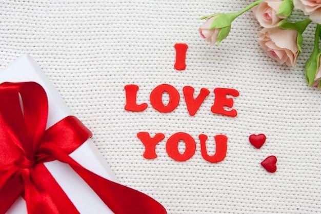 Napis kocham cię czerwonymi literami na białej dzianej powierzchni z kwiatami