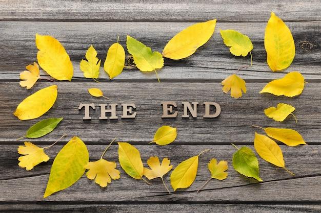 Napis koniec na drewnianym tle, rama żółtych liści