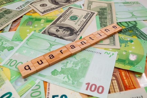 Napis kwarantanna na drewnianych kostkach na fakturze amerykańskich dolarów i banknotów euro