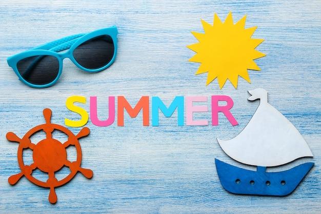 Napis lato z papieru wielobarwnych liter i muszelek oraz letnich i morskich akcesoriów na niebieskim drewnianym stole. lato. relaks. wakacje. widok z góry