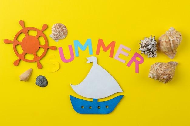 Napis lato z papieru wielobarwnych liter i muszelek oraz statku. lato. relaks. wakacje.
