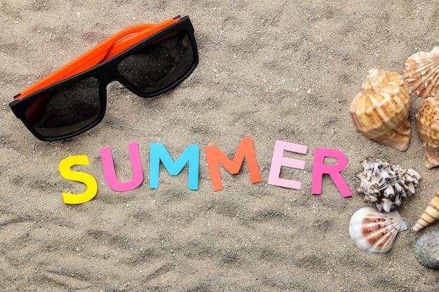 Napis lato z papieru wielokolorowych liter i muszelek oraz letnich dodatków na morskim piasku. lato. relaks. wakacje. widok z góry
