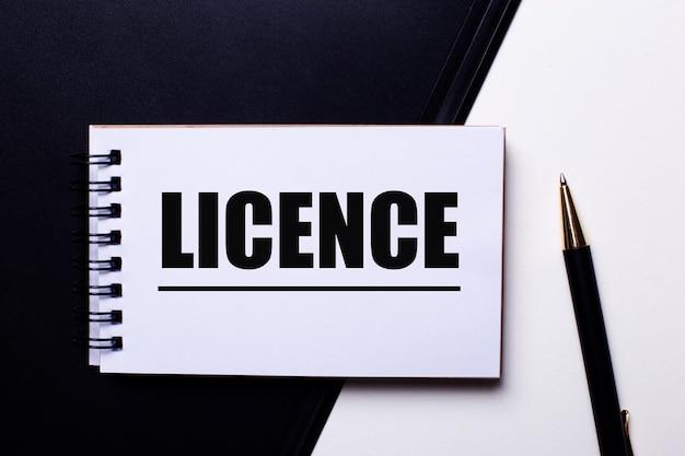 Napis licencja na czerwono na czarno-białej ścianie w pobliżu długopisu