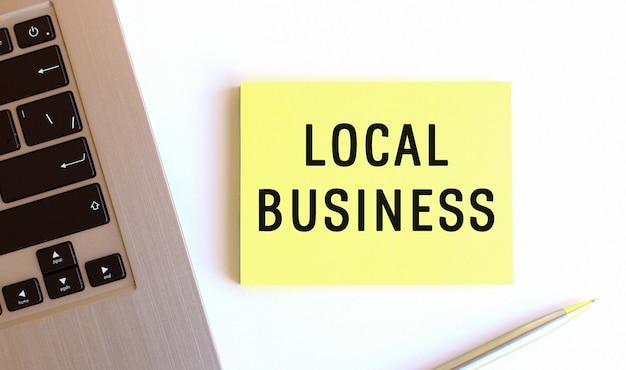 Napis local business na żółtych karteczkach przy laptopie na białym biurku.