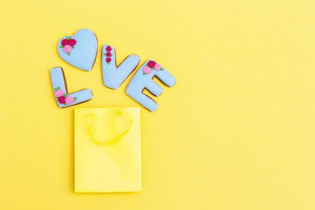 Napis love by domowej roboty ciasteczka z niebieskim lukrem na żółtym pastelowym kolorze. ciastka uciekły z papierowej torby. koncepcja uroczystości.