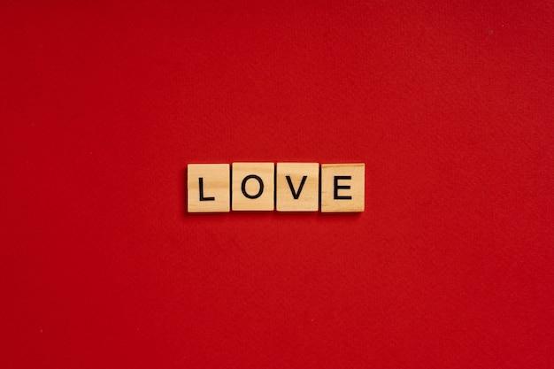 Napis love składa się z drewnianych klocków na czerwonym tle