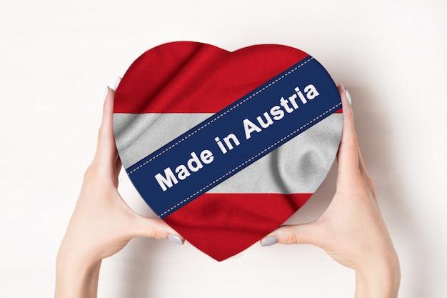 Napis made in austria flag of austria. kobiece ręce trzyma pudełko w kształcie serca. białe tło.