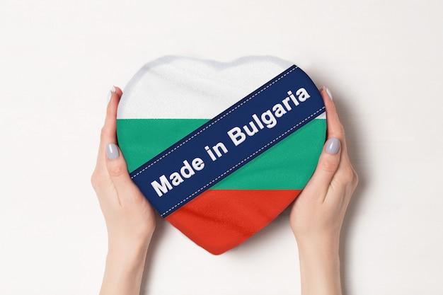 Napis made in bulgaria flag of bulgaria. kobiece ręce trzyma pudełko w kształcie serca. .