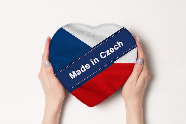 Napis made in czech flag of czech. kobiece ręce trzyma pudełko w kształcie serca. .