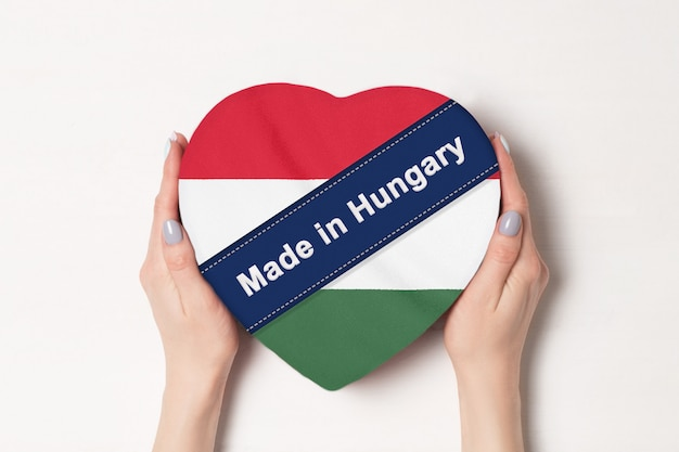 Napis made in hungary flaga węgier. kobiece ręce trzyma pudełko w kształcie serca. .