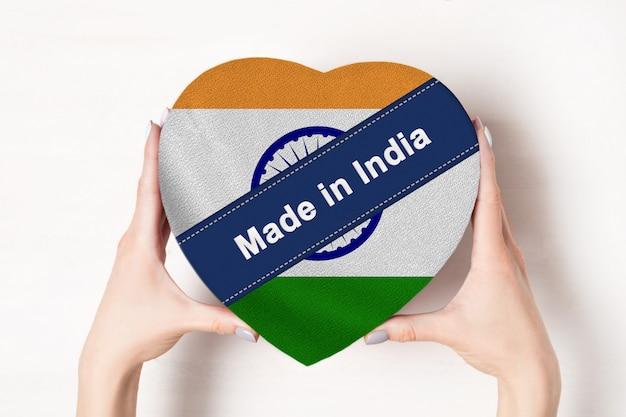 Napis made in india, flaga indii. kobiece ręce trzyma pudełko w kształcie serca.