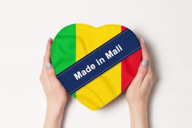 Napis made in mali flagą mali. kobiece ręce trzyma pudełko w kształcie serca. biały
