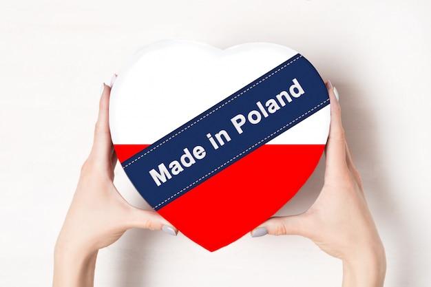 Napis made in poland flag of poland. kobiece ręce trzyma pudełko w kształcie serca. .