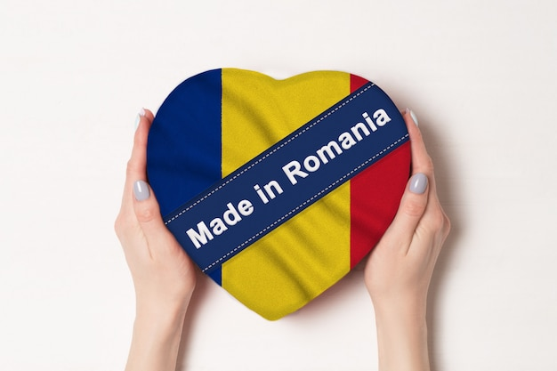Napis made in romania flag of romania. kobiece ręce trzyma pudełko w kształcie serca.