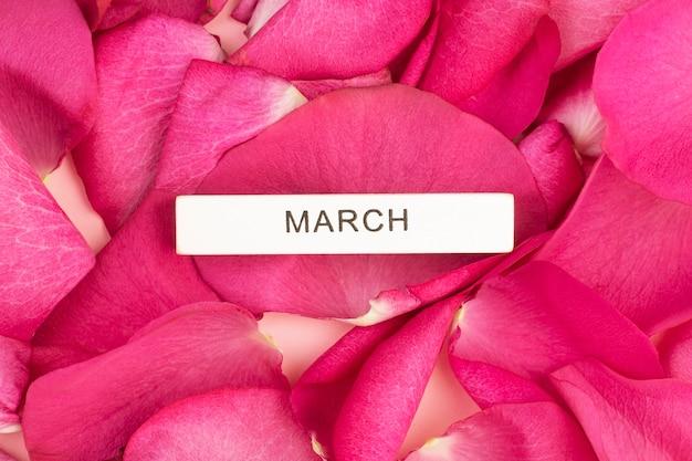 Napis march na tle płatków róż