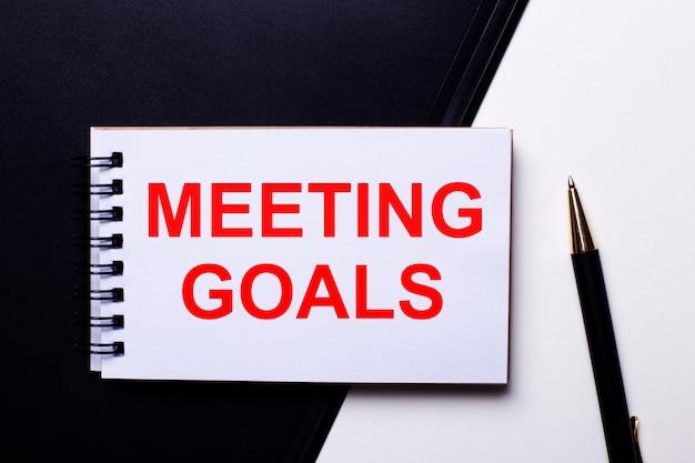 Napis meeting goals w kolorze czerwonym na czarno-białym tle obok pióra