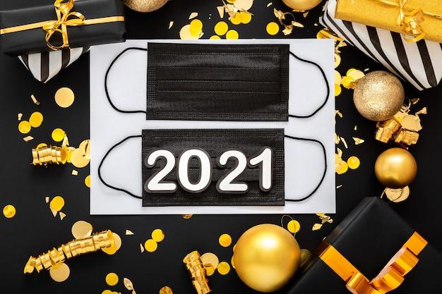 Napis na 2021 r. z czarnymi medycznymi maskami na twarz, złoty świąteczny wystrój. noworoczny covid 19.