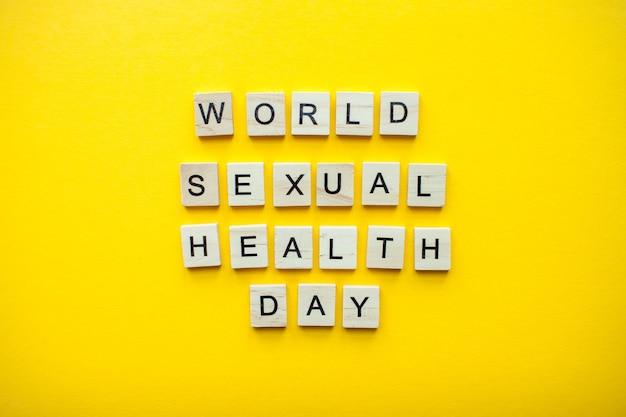 Napis na światowy dzień zdrowia seksualnego z drewnianych klocków na jasnożółtym tle