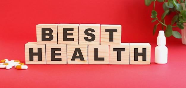Napis najlepsze zdrowie składa się z drewnianych kostek na czerwonym tle z lekarstwami.