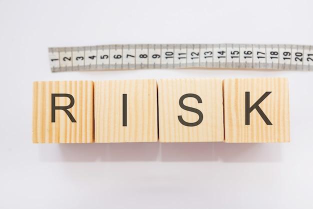 Napis o ryzyku na klockach przy ruletce na białym tle. koncepcja wielkości ryzyka.