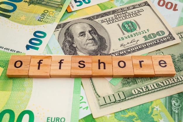 Napis offshore na drewnianych kostkach na fakturze dolarów amerykańskich i banknotów euro