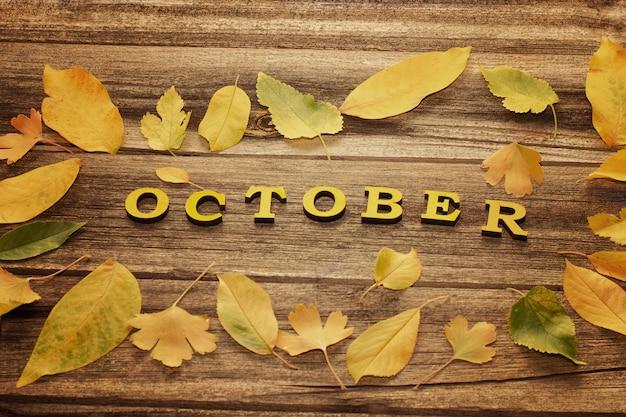 Napis październik na drewnianej desce, rama żółtych liści
