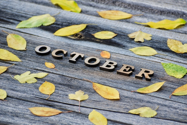 Napis października na drewnianej desce z żółtymi liśćmi