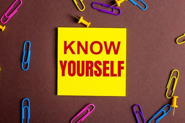 Napis poznaj siebie jest napisany na czerwono na żółtej naklejce na brązowym tle obok kolorowych spinaczy.
