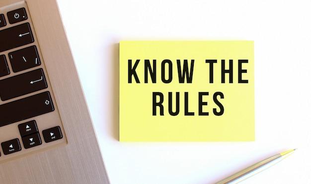 Napis poznaj zasady na żółtych karteczkach samoprzylepnych obok laptopa na białym biurku.